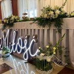 stół przystrojony kwiatami, podświetlony napis miłość
