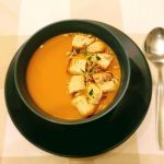 zupa dyniowa z grzankami w czarnym talerzu