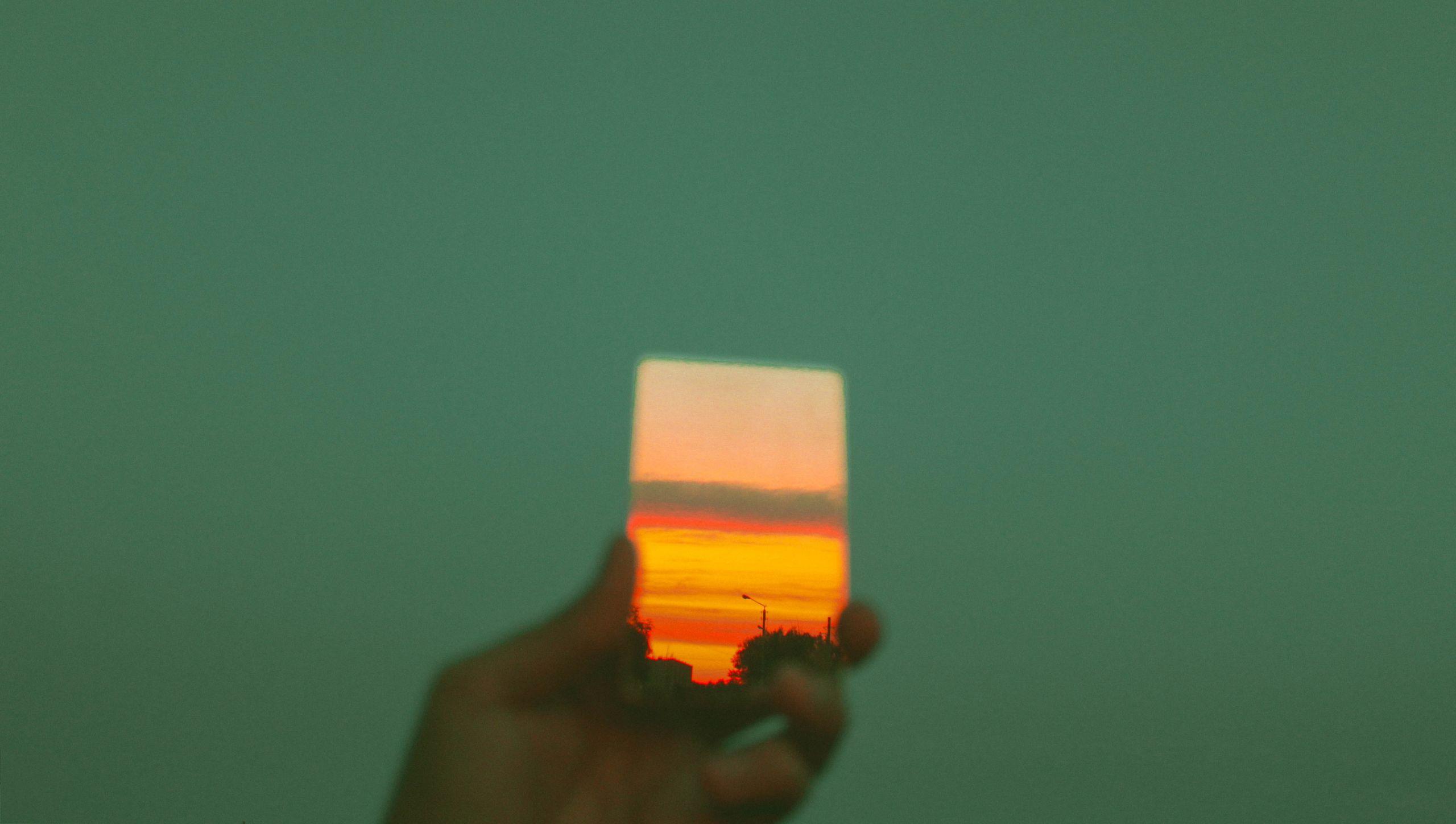 zielone tło, ręka z lusterkiem odbijającym zachód słońca