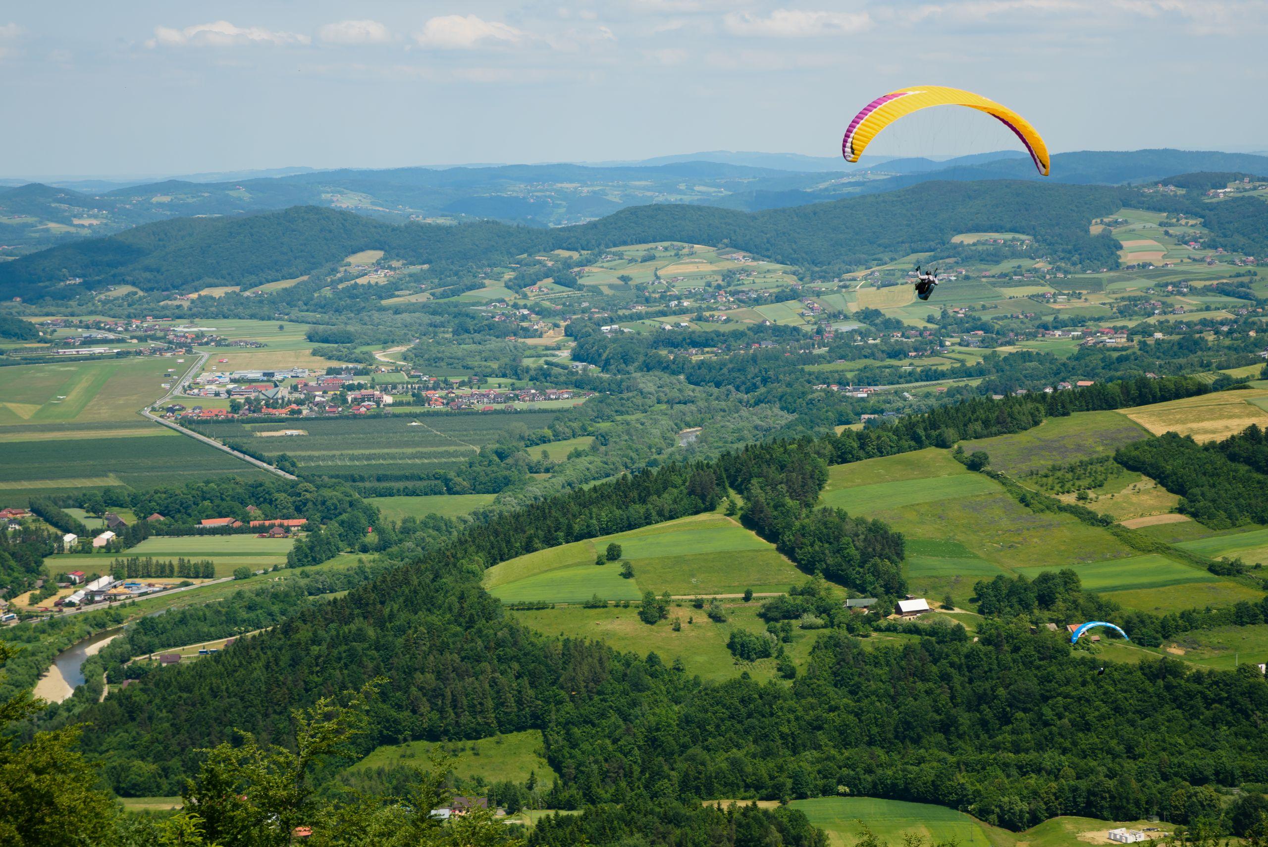 Zielony krajobraz z żółtym spadochronem na pierwszym planie