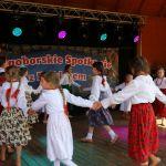 dzieci w strojach ludowych tańczące na scenie