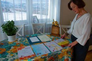 Kobieta stojąca przy stole na którym są rozłożone dyplomy